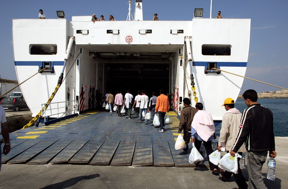 Men embark on a ferryboat leaving for a temporary holding center for foreign nationals in Sicily on June 17, 2005.