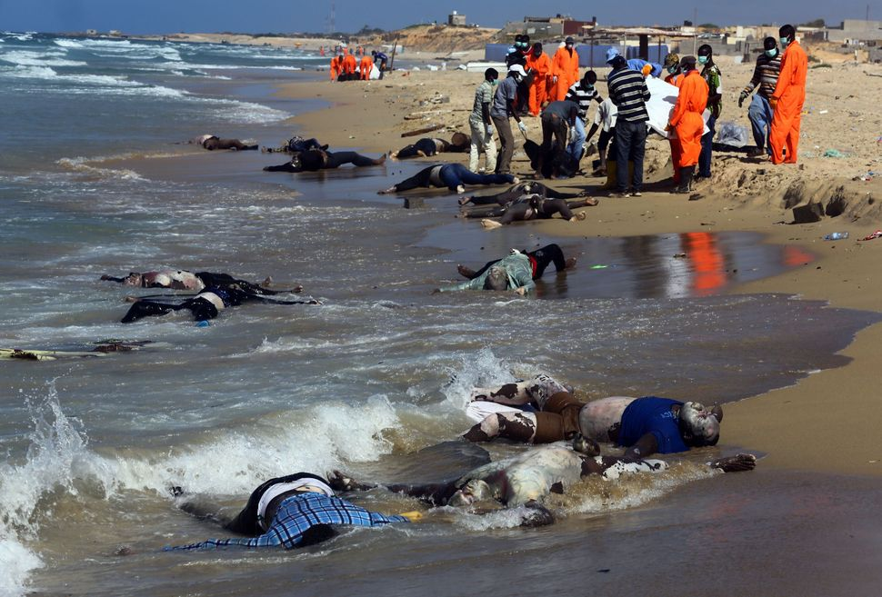 Rescue workers pull the bodies of migrants onto shore east of Tripoli, Libya, on August 25, 2014.