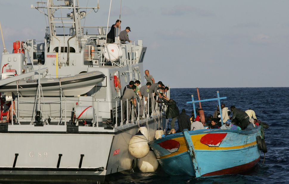 An Italian Customs Service boat takes migrants on board off the coast of Lampedusa, Italy, on June 10, 2005.