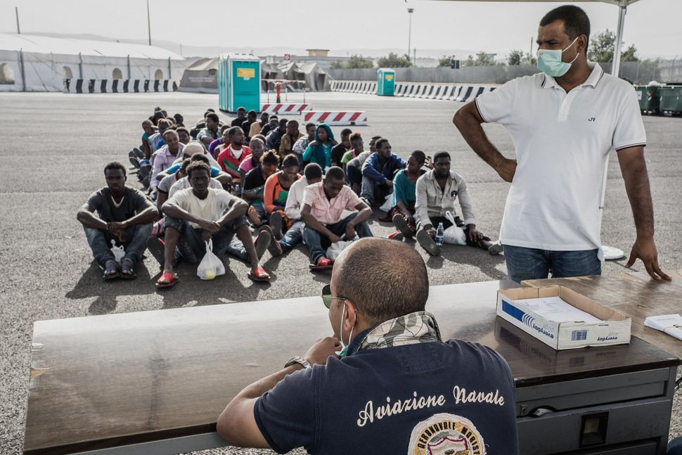 Recently arrived and rescued North African men await processing by Italian immigration authorities in Sicily on Oct. 15, 2014