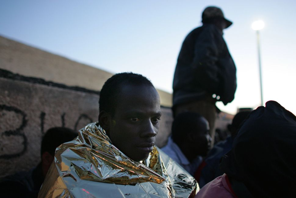 Men wait to be sent to a temporary holding center for foreign nationals on June 10, 2000, in Lampedusa, Italy.