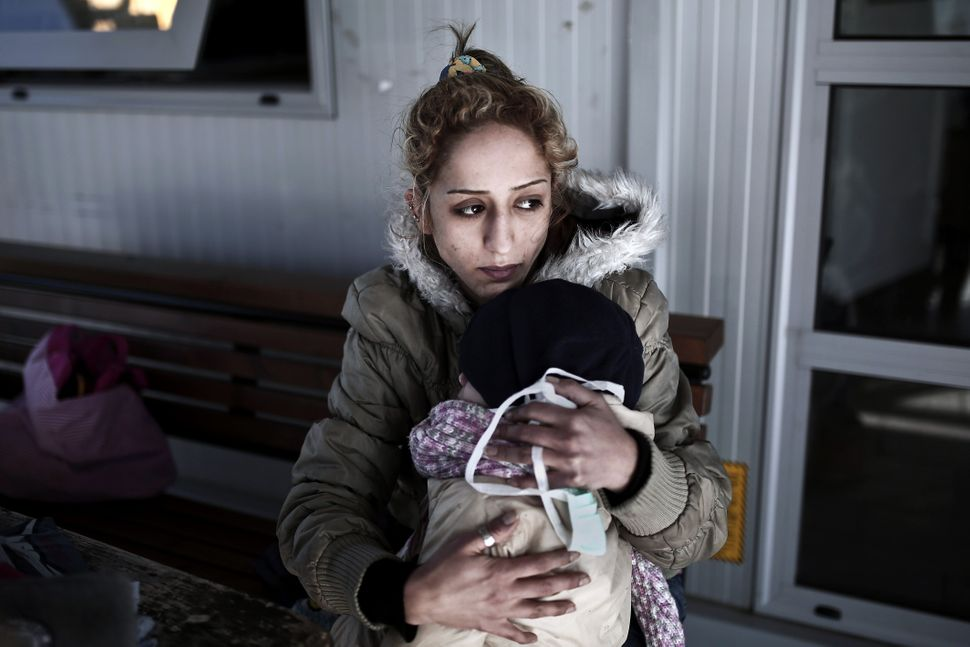 A shipwrecked woman holds her child after disembarking from a rescue vessel in the port of Lesvos island, Greece, on April 17
