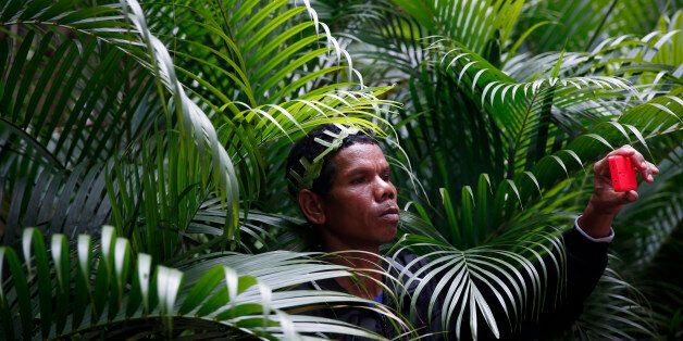 An Orang Asli man, the indigenous minority peoples of Peninsular Malaysia, takes pictures with his mobile phone during a prot