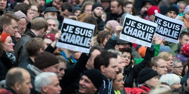 People hold up posters reading 'Je suis Charlie - Aber nicht Pegida' (I am Charlie - But not Pegida) during a rally themed 'F