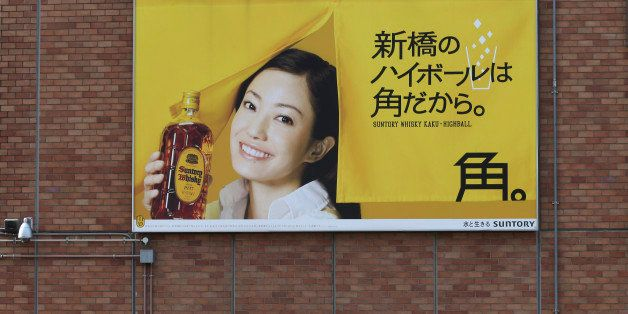People stand under a huge whisky advertisement of Suntory Holdings Ltd., a Japanese beverage company, in front of Shimbashi S