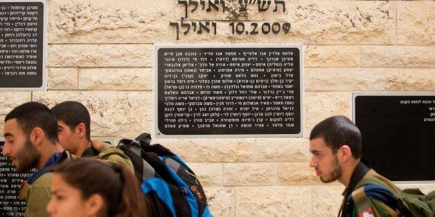 Israeli soldiers walk past a memorial stone in Hebrew bearing the name of Mohammed Abu Khdeir (3rd name from R to L), a Pales