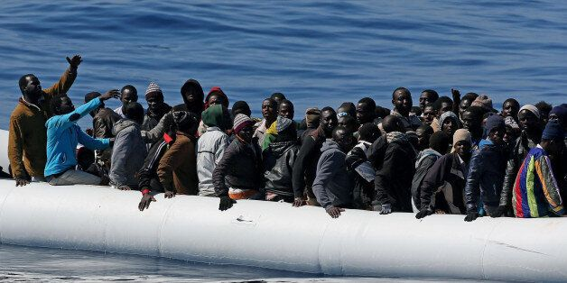 """In this photo made available Thursday, April 23, 2015, migrants crowd and inflatable dinghy as rescue vassel """" Denaro """" (not"""