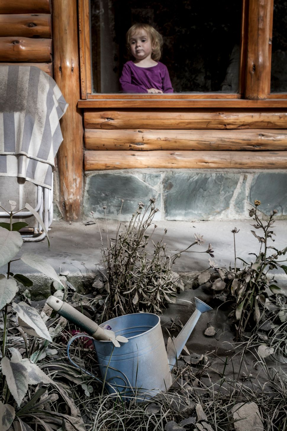 A girl looks through a window as volcanic ash from Chile's Calbuco volcano covers her garden in Villa La Angostura, southern