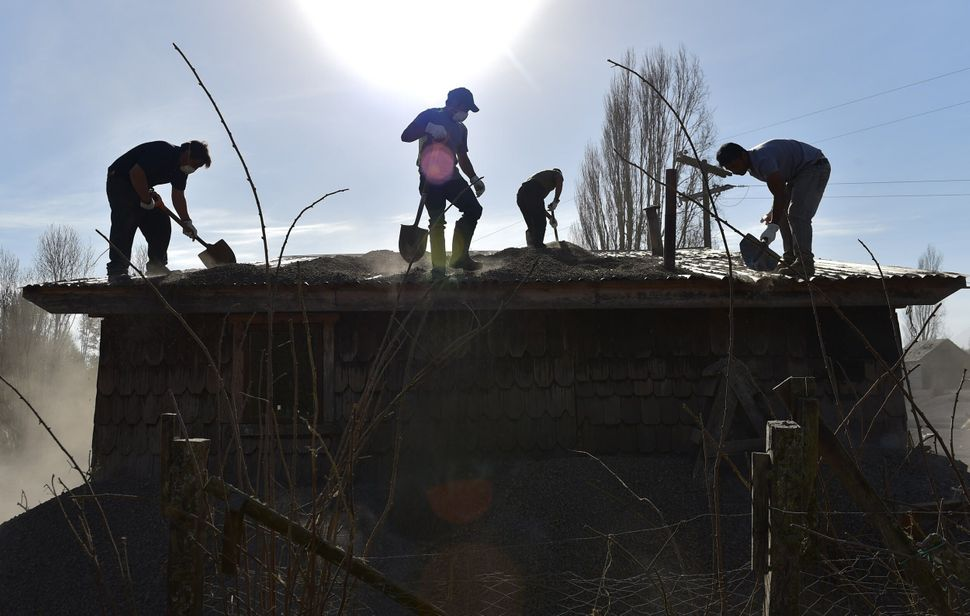 Men remove ash from the roof of a house in La Ensenada, Chile. Southern Chile remained on alert Friday for another eruption f