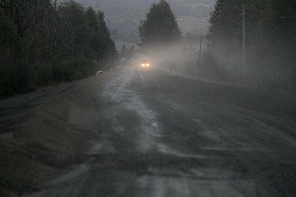 A car passes through a road covered with ash from the eruption of the Calbuco volcano in Puerto Varas, Chile, April 23, 2015.