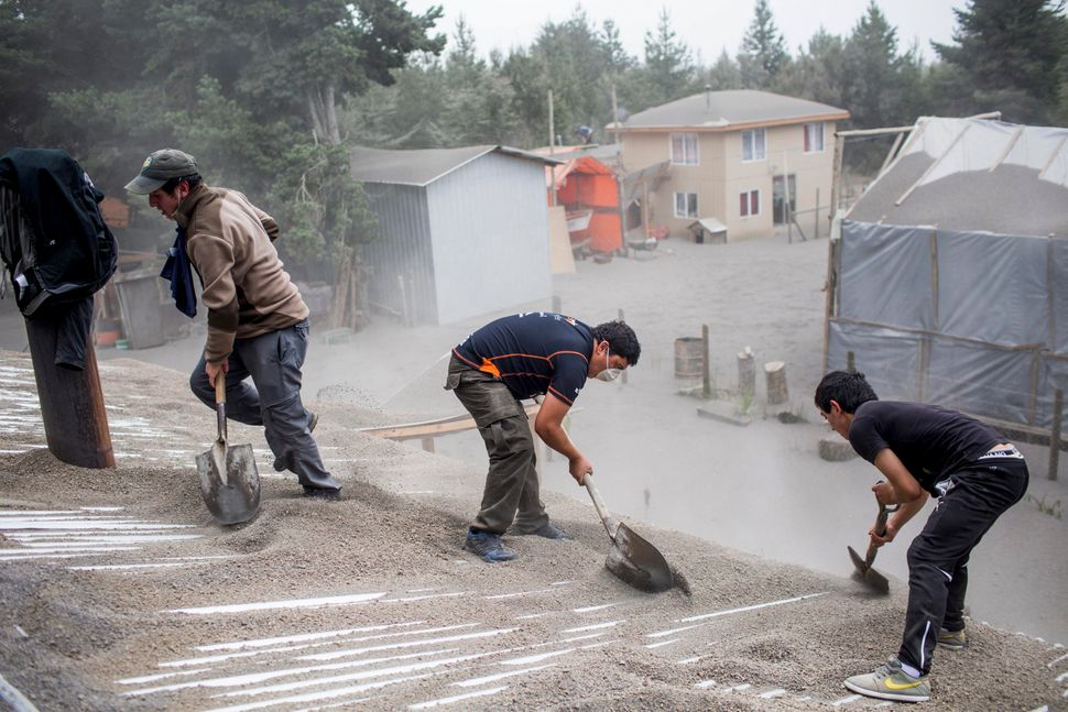 Men remove ash from a building's roof, left by the Calbuco volcano in Ensenada, Chile. The volcano erupted Wednesday for the