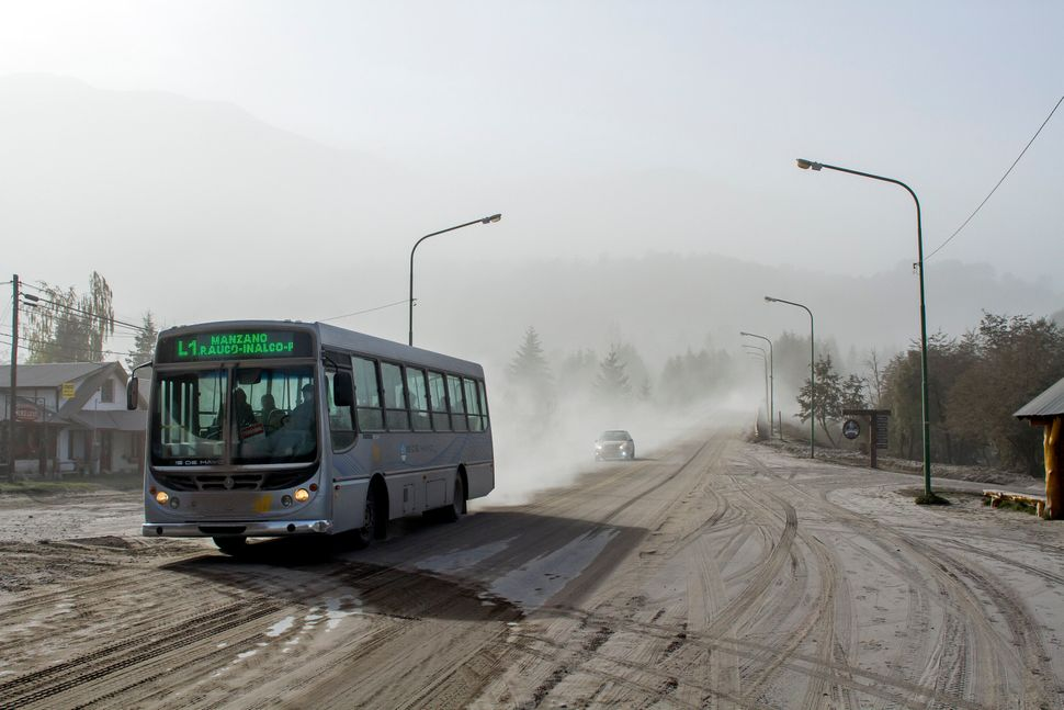 A bus drives along an ash covered road in Villa La Angostura, in southern Argentina, April 23, 2015. The volcano erupted Wedn