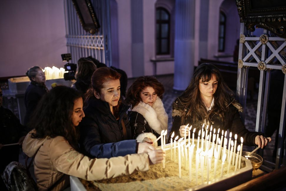 People light candles during a commemoration service at the Armenian Patriarchate in Istanbul on April 24, 2015.