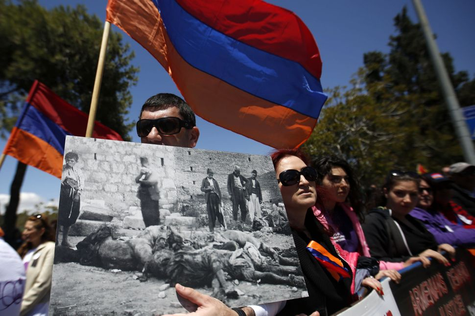 Members of the Armenian community hold Armenian flags during a demonstration to commemorate the genocide anniversary in front