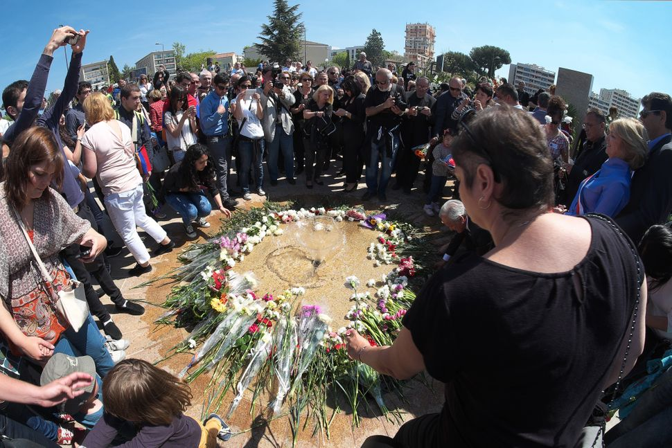 People lay flowers as they gather to pay their respects during a ceremony at the Memorial of the Armenian Genocide in Marseil