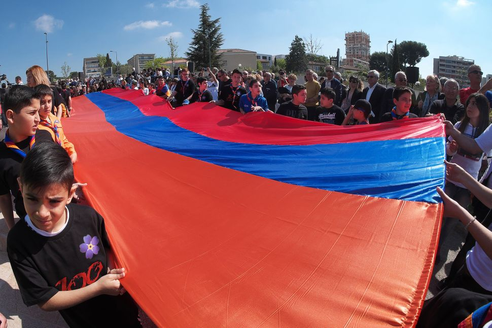 Youths unfurl the Armenian flag during a ceremony at the Memorial of the Armenian Genocide in Marseille on April 24, 2015.