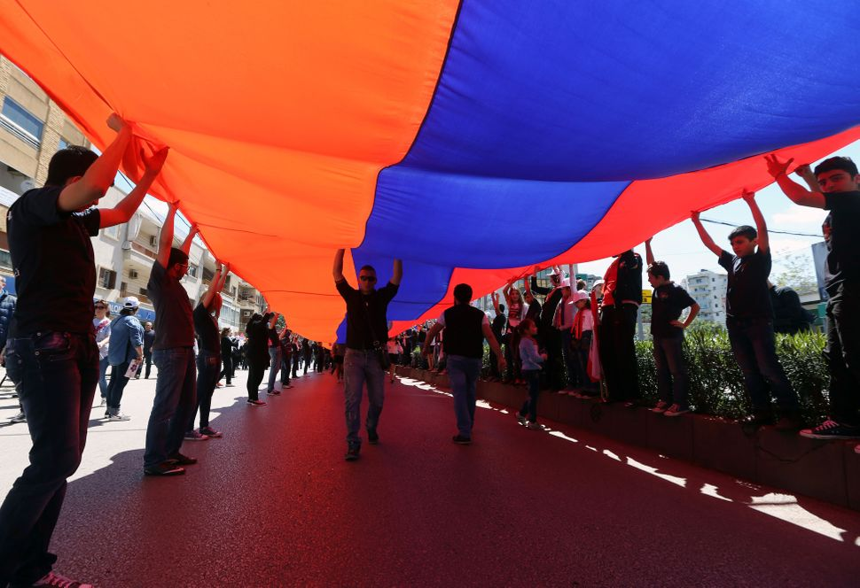 Armenians in Lebanon hold up a giant Armenian flag during a march on April 24, 2015, to mark the 100th anniversary of the mas