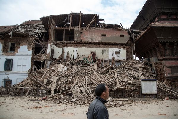 A Kathmandu resident passes in front of a collapsed temple at Basantapur Durbar Square on April 25, 2015, in Kathmandu, Nepal