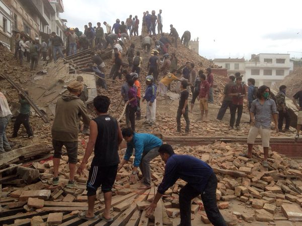 Volunteers help with rescue work at the site of a building that collapsed in Kathmandu, Nepal, April 25, 2015. (AP Photo/ Nir