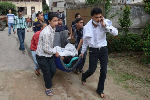 Nepalese health workers carry injured people into an open area following an earthquake, at Lalitpur on the outskirts of Kathm