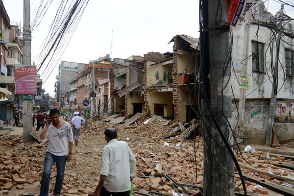 Nepalese people walk past collapsed buildings at Lalitpur, on the outskirts of Kathmandu, on April 25, 2015.  (PRAKASH MATHEM
