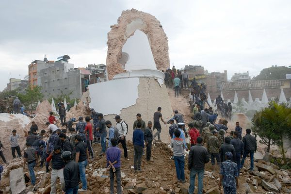 Nepalese rescue members and onlookers gather at the collapsed Dharahara Tower in Kathmandu on April 25, 2015. (PRAKASH MATHEM