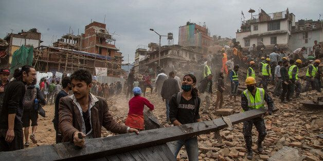 KATHMANDU, NEPAL - APRIL 25: Emergency rescue workers clear debris in Basantapur Durbar Square while searching for survivors