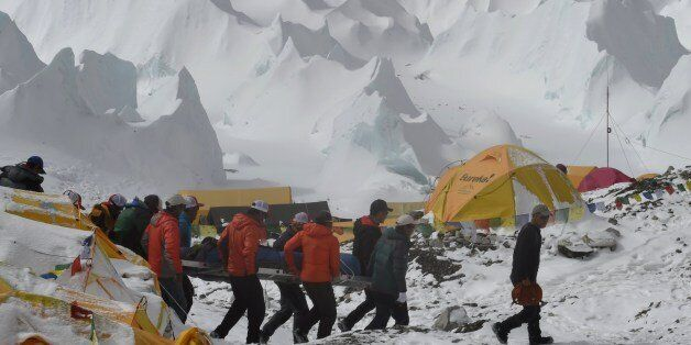 Rescue team personnel carry an injured person towards a waiting rescue helicopter at Everest Base Camp on April 26, 2015, a d