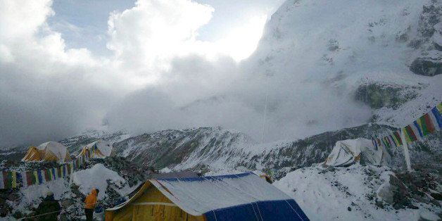 This photo provided by Azim Afif, shows a small avalanche on Pumori mountain as seen from Everest Base Camp, Nepal on Sunday,