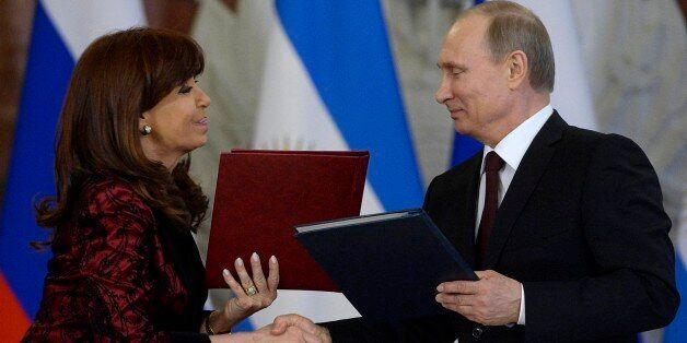Russian President Vladimir Putin, right, and Argentina's President Cristina Fernandez exchange documents at a signing ceremon