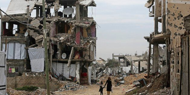 Palestinian children walk between the rubble of buildings which were destroyed during the summer 2014 Israel-Hamas war, in th