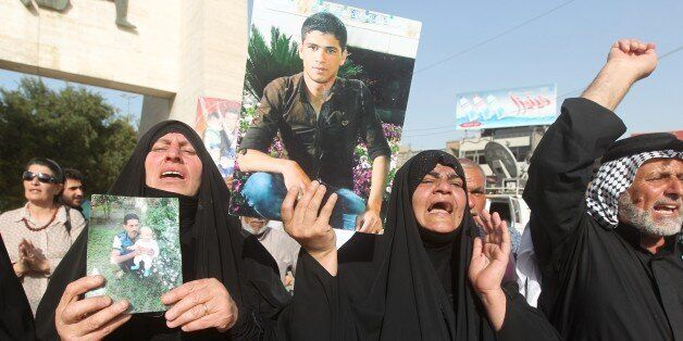 Iraqi women hold pictures of their relatives, who are believed to have been killed in the Speicher massacre, during a demonst
