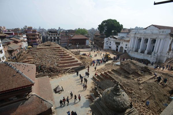 People walk by the earthquake damaged Durbar Square in Kathmandu on April 28, 2015. Hundreds of thousands of Nepalis spent an