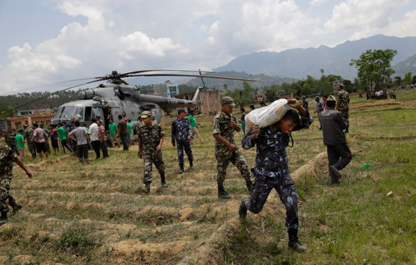 Nepalese soldiers unload relief material brought in an Indian air force helicopter for victims of Saturday'€™s earthquake at
