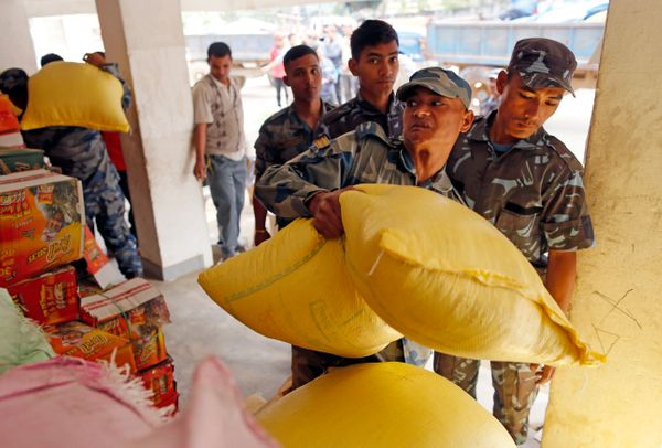 Nepalese soldiers stack bags of grain at a relief staging area near Saturday's massive earthquake's epicenter in the town of