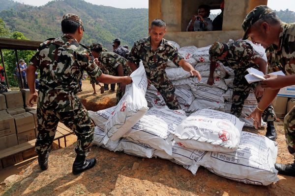 Nepalese soldiers load U.S. AID relief sacks at landing zone near Saturday's massive earthquake's epicenter in the town of Go