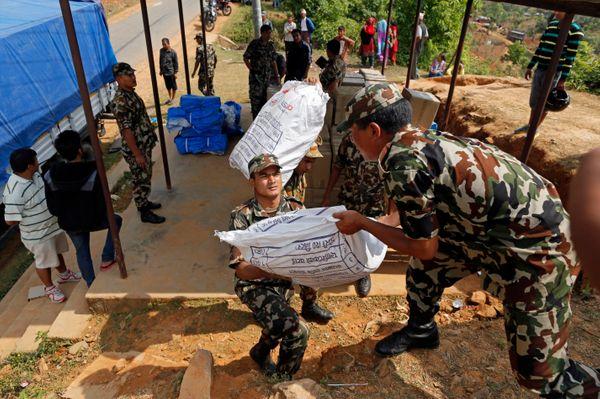 Nepalese soldiers load U.S. AID relief sacks at a staging area near Saturday's massive earthquake's epicenter in the town of