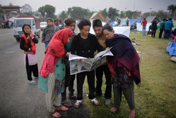 Survivors of Saturday's earthquake read newspaper at a makeshift camp in Kathmandu, Nepal, Tuesday, April 28, 2015. A strong