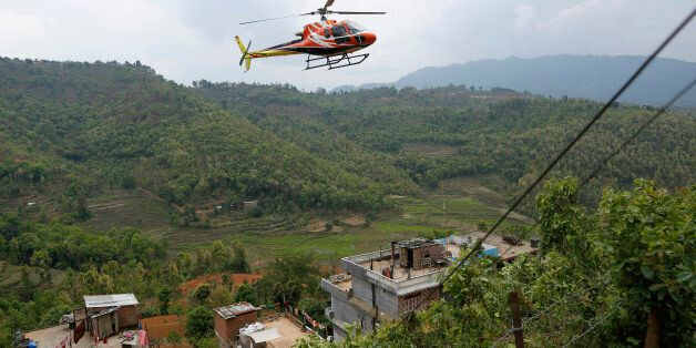 A chartered helicopter carrying injured villagers from Saturday's massive earthquake arrives from the heavily-damaged Ranacho