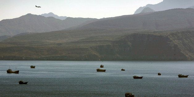 In this Jan. 19, 2012 photo, a plane flies over the mountains in south of the Strait of Hormuz as the trading dhows and ships