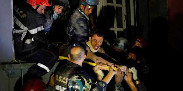 Survivor Rishi Khanal, 27, is freed by French rescuers from the ruins of a three-story hotel in the Gangabu area of Kathmandu