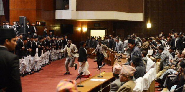 Nepalese opposition lawmakers rush to block ruling party leader Chin Kazi Shrestha (C-R) at the parliament during a constitue
