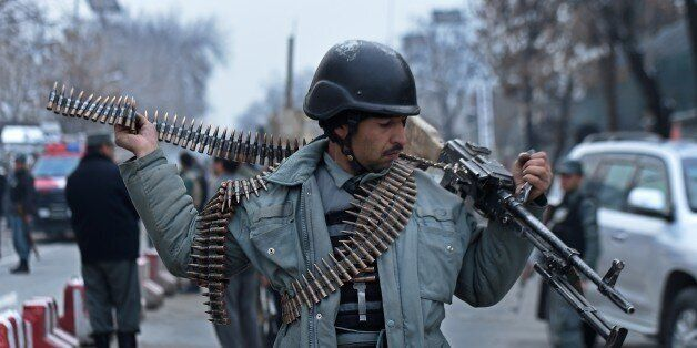 An Afghan policeman adjusts his weapon as he stands at the scene of a suicide attack on a Turkish diplomatic vehicle in front