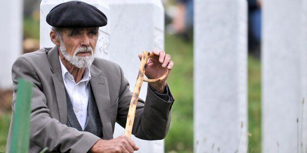 An elderly Bosnian Muslim man, survivor of the Srebrenica 1995 massacre, pays his respects at a relative's grave at the Srebr