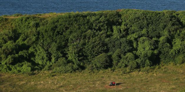 HELGOLAND, GERMANY - AUGUST 04:  A couple sits on a bench in grass that covers a crater created by a 5-ton bomb, the largest