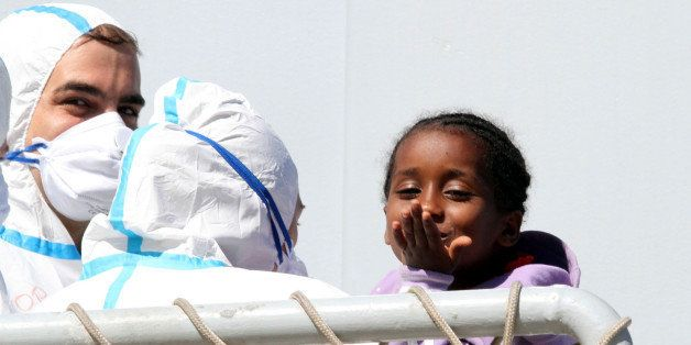 A child blows a kiss as migrants disembark from the Italian Navy frigate Bersagliere at the Reggio Calabria harbor, Italy, Mo