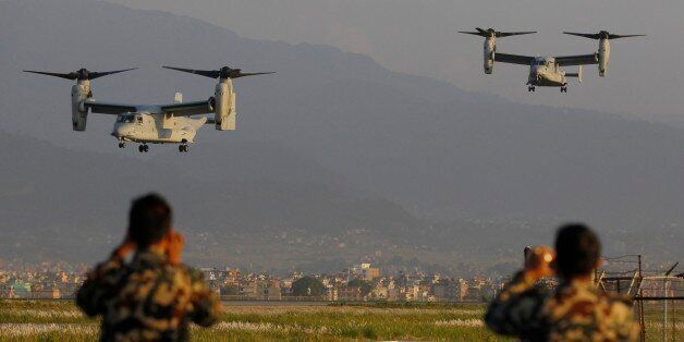 Nepalese soldiers take pictures as US Air Force Bell Boeing V-22 Osprey aircrafts arrive at the Tribhuvan International airpo