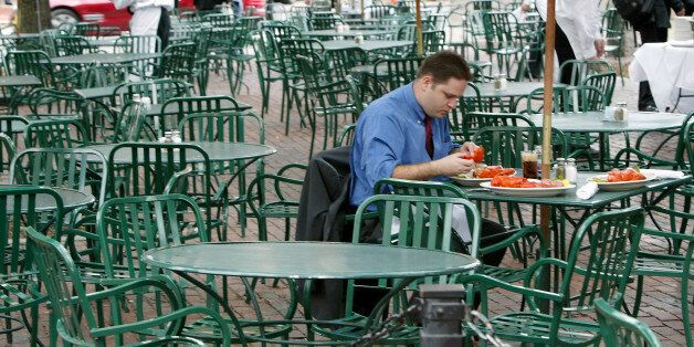 An unidentified patron eats lobsters at a deserted outdoor cafe in Faneuil Hall in Boston Tuesday, July 27, 2004. The Democra