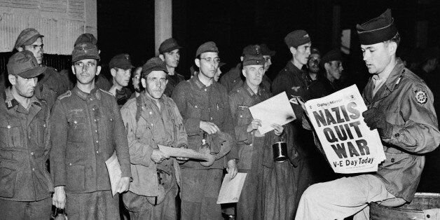 Pfc. Clarence K. Ayers of Evansville, Ind., reads the news of V-E Day as newly arrived German prisoners stand of a New York C