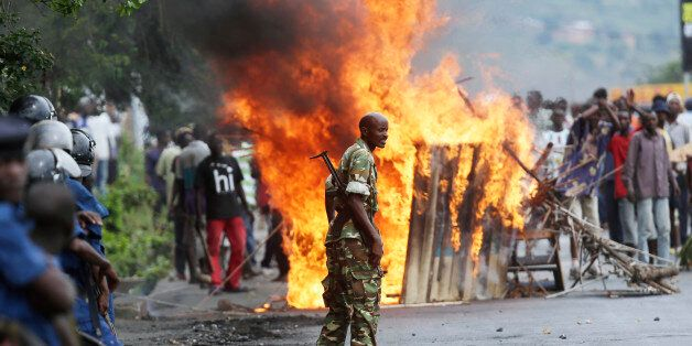 A soldier stands between demonstrators and riot police facing off in the Musaga district of  Bujumbura, Burundi, Monday May 4